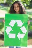 Young environmental activist smiling at the camera holding a poster Stock Image