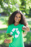 Young environmental activist smiling at the camera holding a potted plant Royalty Free Stock Images