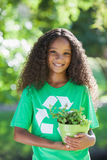 Young environmental activist smiling at the camera holding a potted plant Royalty Free Stock Photos