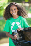Young environmental activist smiling at the camera picking up trash Stock Photography