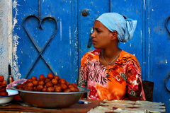 Young Ethiopian fruit seller. A young woman selling fruits in a street of Harar, Ethiopia. The African country is struggling to survive against endemic issues as stock images