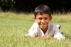 Young ethnic boy lying on the grass in park Stock Photo