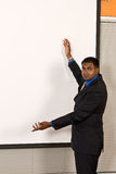 Young ethnic business man at an off-white projector screen. Young ethnic business man makes a gesture with his arms at an off-white projector screen Royalty Free Stock Photos