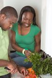 Young ethnic couple on kitchen slicing vegetables. Young black African American couple preparing vegetable salad on kitchen countertop Stock Photography