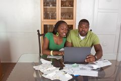 Young ethnic couple paying bills over internet. Financial advisor helping organize and optimize home finances bills, Young black African American couple sitting Royalty Free Stock Images