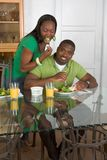 Young ethnic couple by table eating breakfast Royalty Free Stock Images