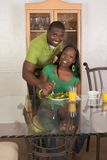 Young ethnic couple by table eating breakfast Royalty Free Stock Photo