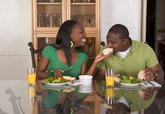 Young ethnic couple by table eating breakfast royalty free stock photos