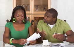 Young ethnic couple by table overwhelmed by bills. Young black African American couple sitting by glass table and trying to work through pile of bills