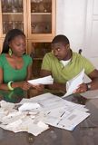 Young ethnic couple by table overwhelmed by bills. Young black African American couple sitting by glass table and trying to work through pile of bills Royalty Free Stock Images