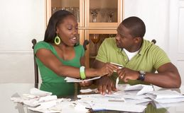 Young ethnic couple by table overwhelmed by bills Stock Image