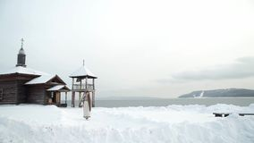 A young ethnic girl goes from the Church and the bell tower along the path. Snow, water and mountains in the background stock footage