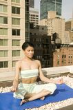 Young ethnic girl practising yoga. Attractive young ethnic brunette girl practices yoga on a manhattan city roof top Stock Image