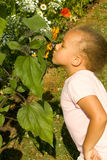 Young Ethnic Girl smelling the flowers. In the garden Stock Image