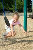 Young Ethnic Girl in Swing. A young ethnic girl has fun playing on the swing in the park Stock Image