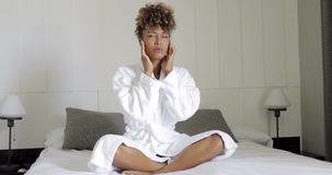 Girl suffering pain on bed. Young ethnic girl in white bathrobe sitting with eyes closed on bed and grimacing from headache or migraine stock video footage