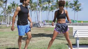 Couple doing fitness in the park. Young ethnic man and woman standing and interacting while doing fitness on green lawn in sunny park stock footage