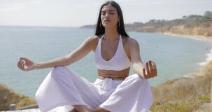 Girl meditating on shoreline stock footage