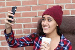 Young ethnic woman taking selfie holding a cup of coffee stock photo