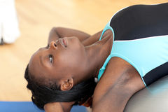 Young ethnic woman working out with a pilates ball Royalty Free Stock Images