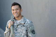 Young ethnically ambiguous American soldier holding backpack royalty free stock photography