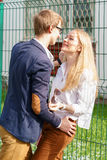 Young european attractive couple is standing and hugging close to green fence under sun. Beautiful woman anticipates kissing from stock photo