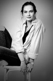 Young European attractive fashion model beautiful eyes is posing in jeans and shirt on chair Stock Photo