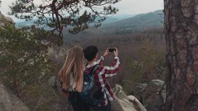 Young European brunette man and blonde girl having a great time together on the top of the mountain, taking photos of. Amazing scenery down the hill. Stormy stock video footage