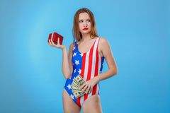 Woman holding a gift box and a bunch of dollar bills and looking away. On a blue background. Young European brunette woman dressed in bodysuits with an American Royalty Free Stock Image