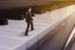 Businessman walking on piano keys. Young european businessman walking on abstract bokeh piano keys. Musician concept. 3D Rendering Stock Photos