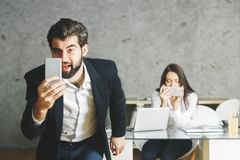 Young european businessman and woman using smartphone Royalty Free Stock Photography