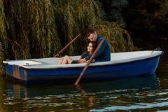 Young european couple is boating on a lake, young man and his girlfriend are sitting into boat at sunset, couple in love. Beautiful european couple is boating on stock image