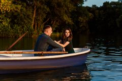 Young european couple is boating on a lake, young man and his girlfriend are sitting into boat at sunset, couple in love. Beautiful european couple is boating on royalty free stock photography