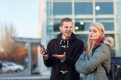 A guy aggressively yells at a girl from behind a broken mobile phone. A young European couple standing on the street, a guy aggressively yells at a girl from royalty free stock photography