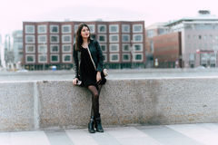 Young European female with classy look dreaming about something while standing alone in urban setting, Royalty Free Stock Image