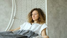 Young European girl in a linen dress keep calm and swinging in a hammock chair, enjoying the rest. Beautiful girl dreams. Young European girl in a linen dress stock video footage