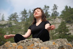 Young European girl meditates in mountains. Royalty Free Stock Image