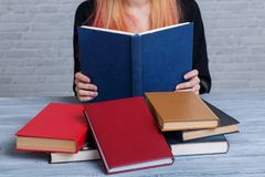 A girl reads a book next to a pile of other scattered books. Learning concept. Stock Photos