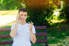 A young European guy in a white T-shirt speaks on the phone and sits on a bench in the city park and points with your finger. The stock photography