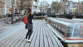 Young European lady walks talking on the phone. Free and easy relaxed walk along wooden river embankment with a boat. 4K. Young European lady walks talking on stock video footage