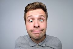Young european man looking on nose. His eyes are squinted look. stock photos