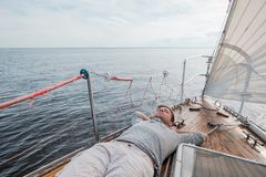 Young european man resting on yacht looking at sky stock photography