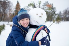 Young european man in warm clothes making snowman from snow outdoor stock image