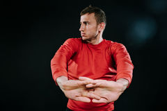 Young European man wearing red sportswear and stretching his hands after a hard workout in dark background. Powerful handsome athl. Caucasian sportsman wearing Royalty Free Stock Image