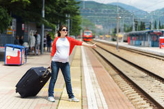 Young european pregnant woman with heavy baggage trying to stop train on railway station for traveling at sunny day royalty free stock photography