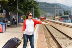 Young european pregnant woman with heavy baggage trying to stop train on railway station for traveling at sunny day. Young european pregnant woman with Stock Images