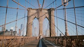 Young European romantic couple spin holding each other, run to camera holding hands at Brooklyn Bridge on a summer day. Happy family relationships of trust stock video