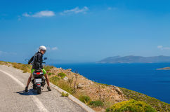 Young european tourist driving scooter looks back while stading. On road roadside with sea in the background, Greek Island, Greece Stock Photo