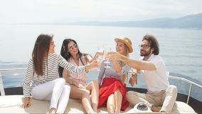 Young european tourists guys and girls celebrating on yacht happy start of their vacation - Group of friends toasting