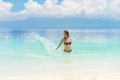 Young european woman in bikini with good mood splashing and dancing in beautiful tropical calm sea under cloudy soft sky Stock Photos